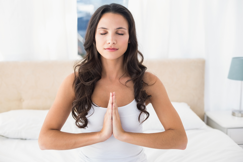 Calm brunette doing yoga on bed at home in bedroom